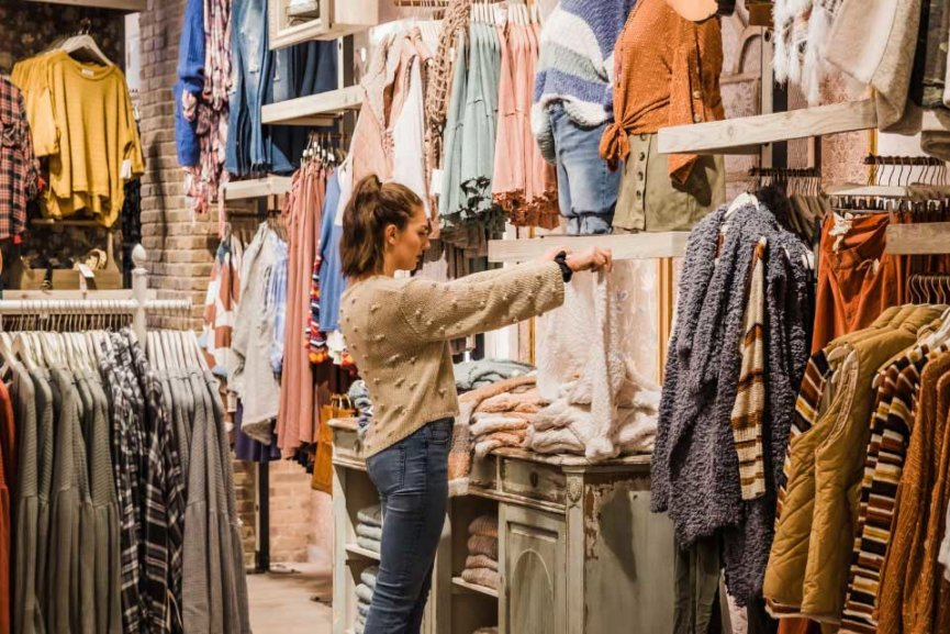 A woman looking at a rack of clothes