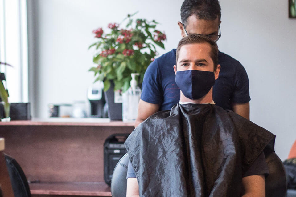 A barber giving a haircut to a man wearing a mask