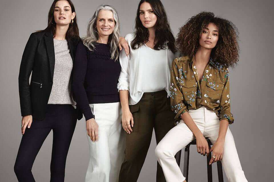 Four woman in a pose modeling designer clothing