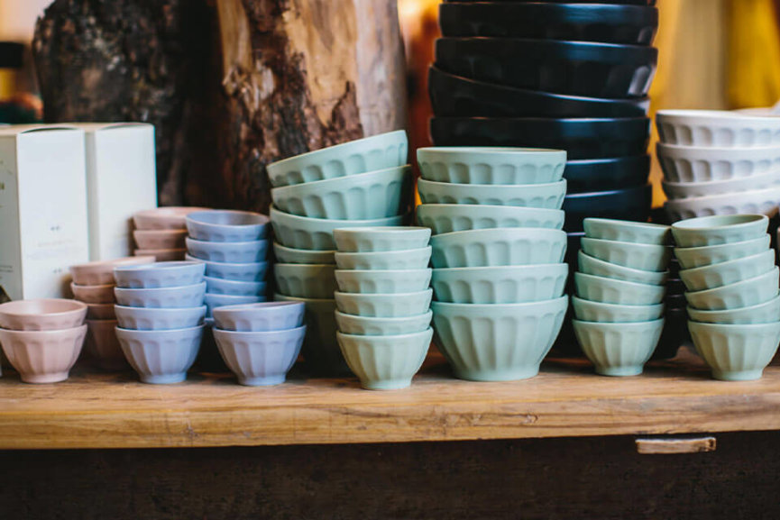Several sets of bowls sitting on a table, they are all different colors and sizes.