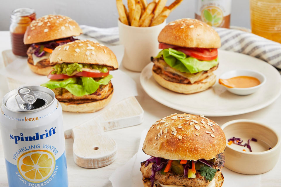 A table with several varieties of hamburgers, french fries, and dipping sauces.