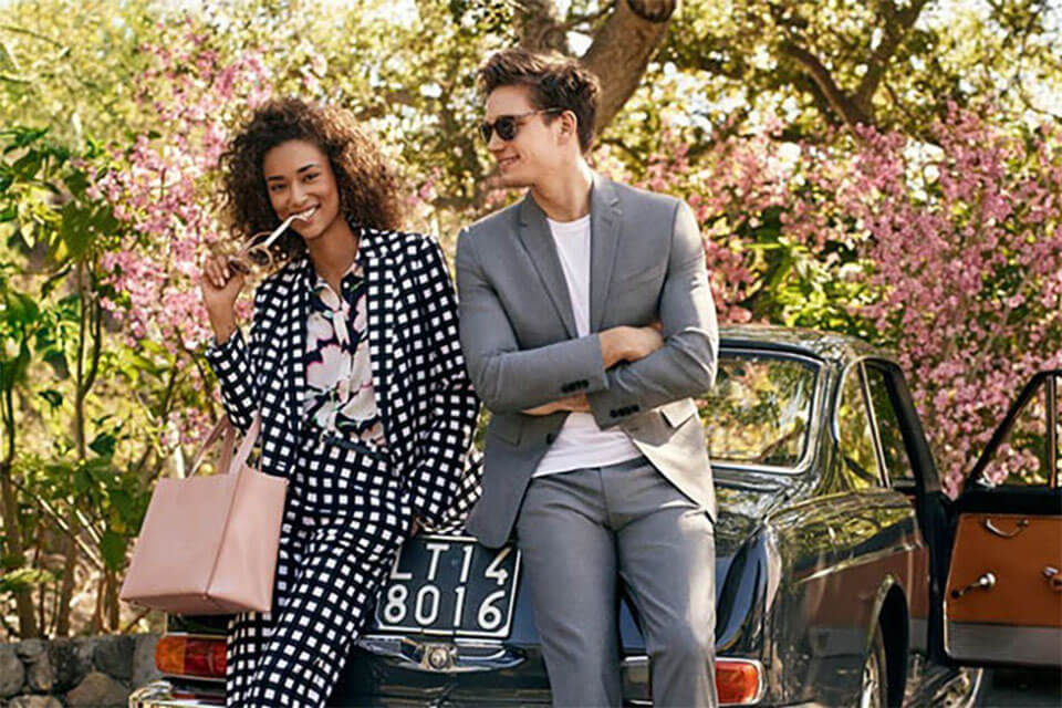 A woman and a man dressed fashionably leaning against a car.