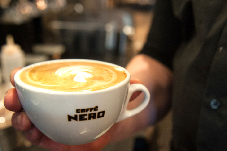 A cup of coffee with Latte Art on the top. It's inside of a white mug that has the Caffe Nero logo on it.