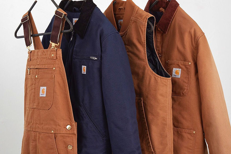 A pair of overalls, and various jackets hanging on a rack.