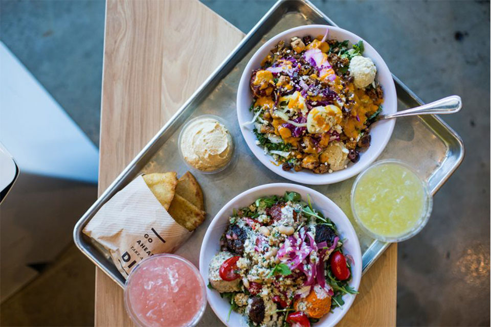 Two bowls of food on a metal tray, sitting next to two colorful drinks.