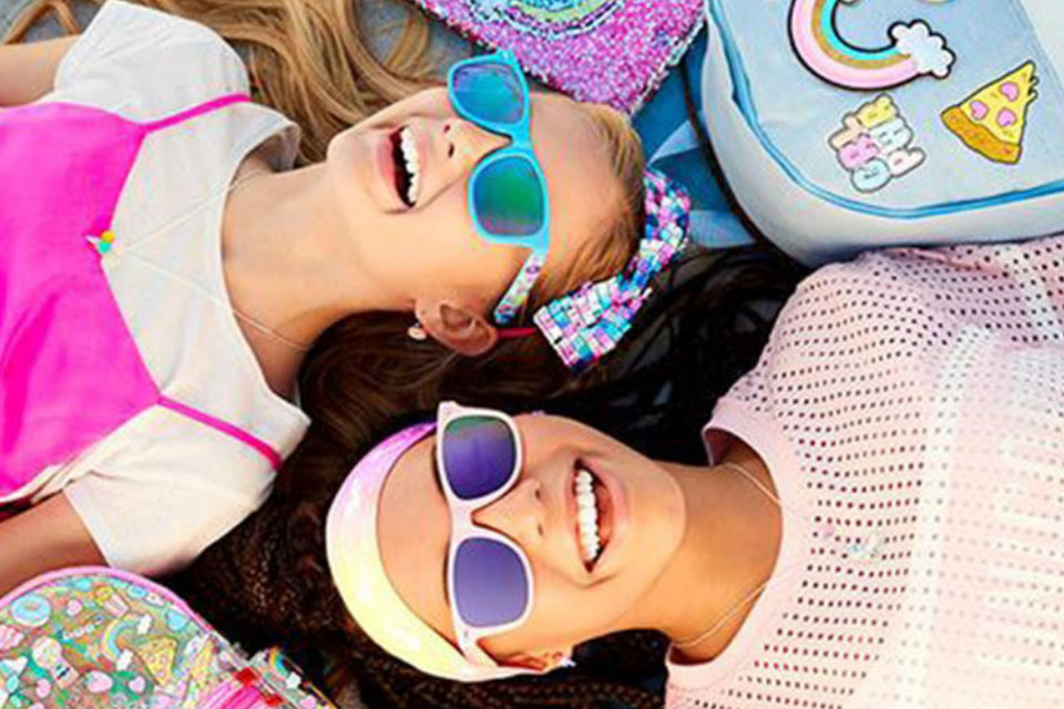 Two girls smiling while looking up at the sky wearing colorful sunglasses