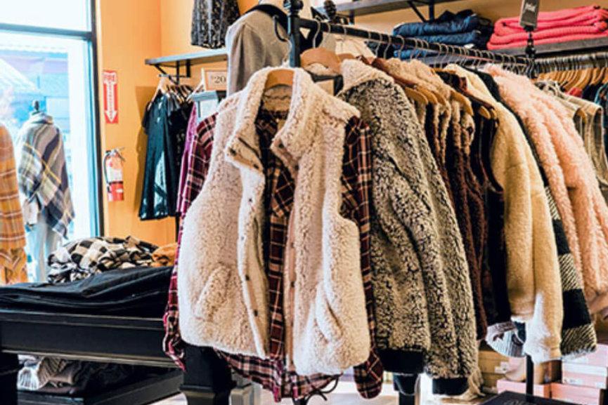 Several coats hanging on a rack inside