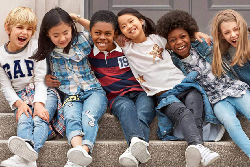 Six kids sitting on a step with their arms around each other waring Gap clothing