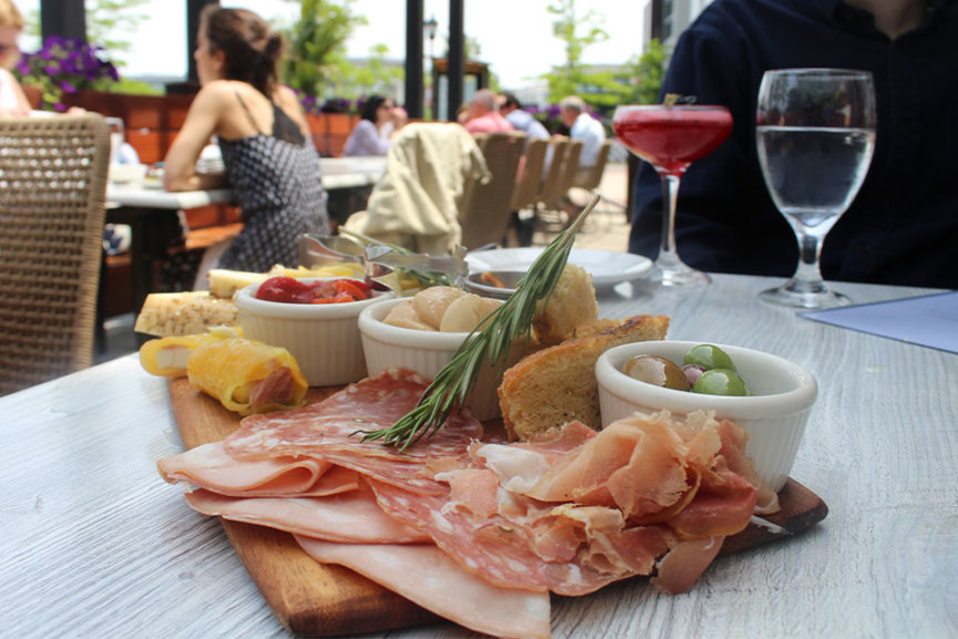 A plate of cold cuts and finger foods on a wood tray
