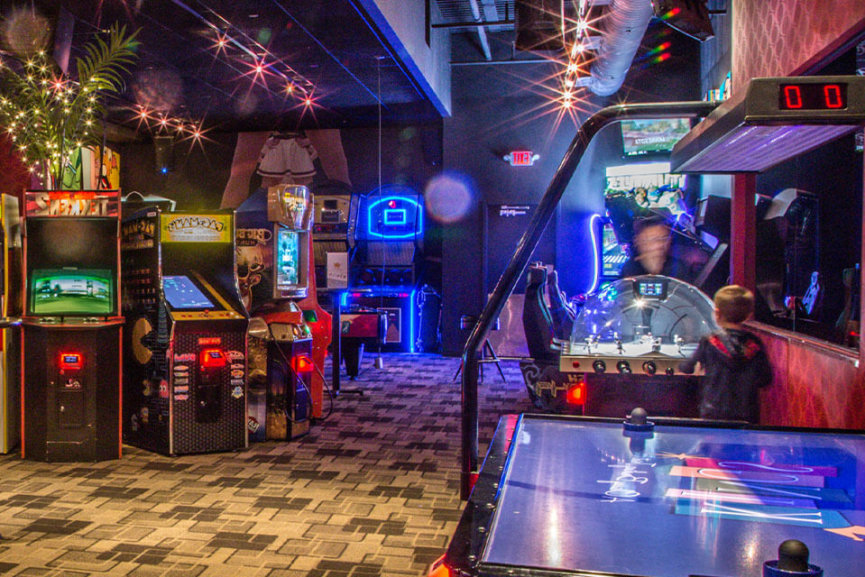 A video arcade with several games and an air hockey table