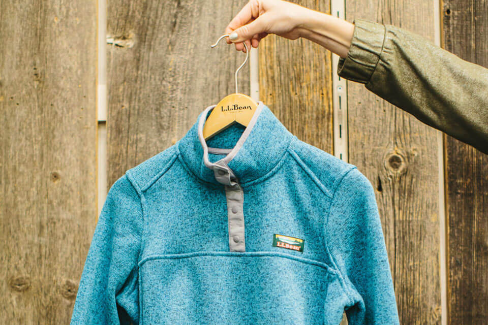 An LL Bean sweater being held up by somone holding a hanger