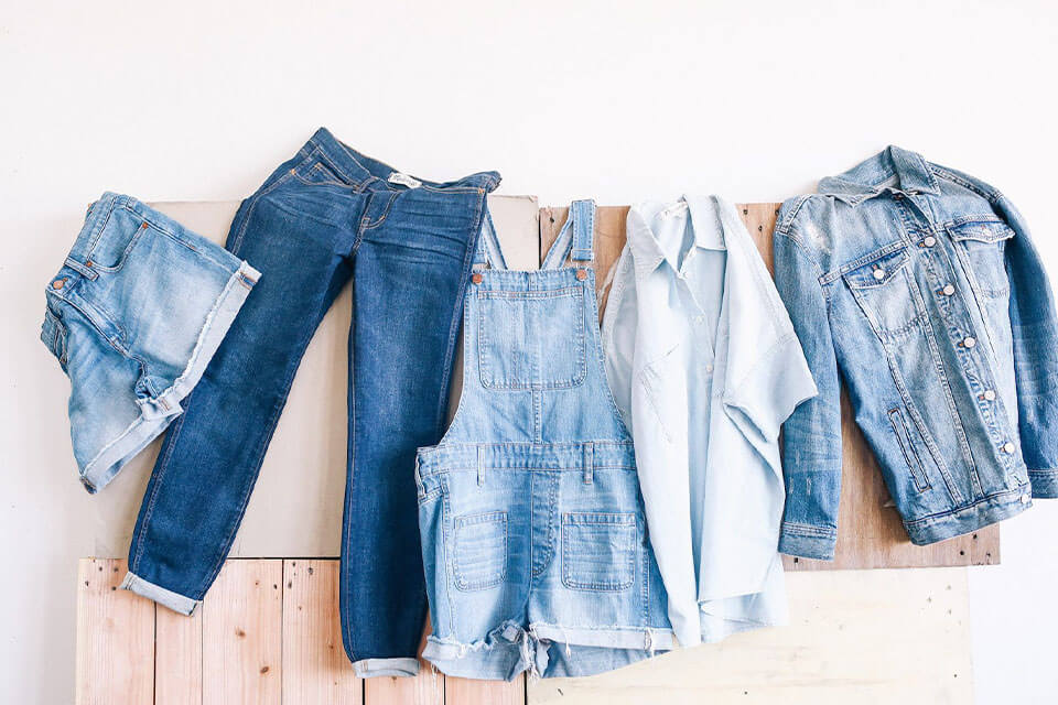 Various jeans and denim clothing hanging up on a wall
