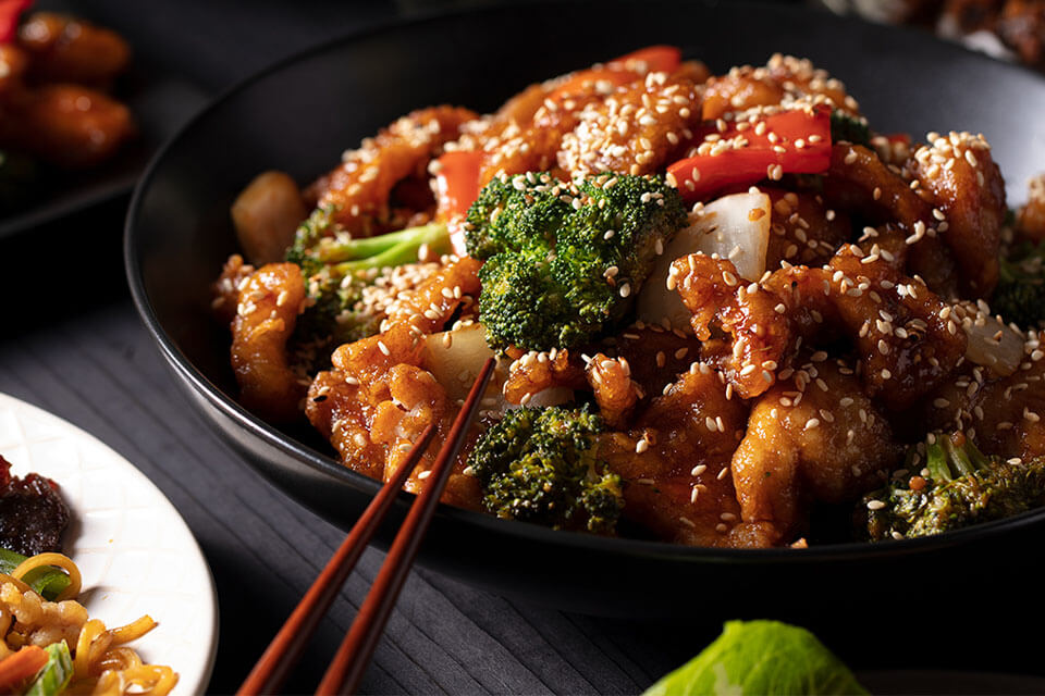 A bowl of sesame chicken, peppers, broccoli, and rice