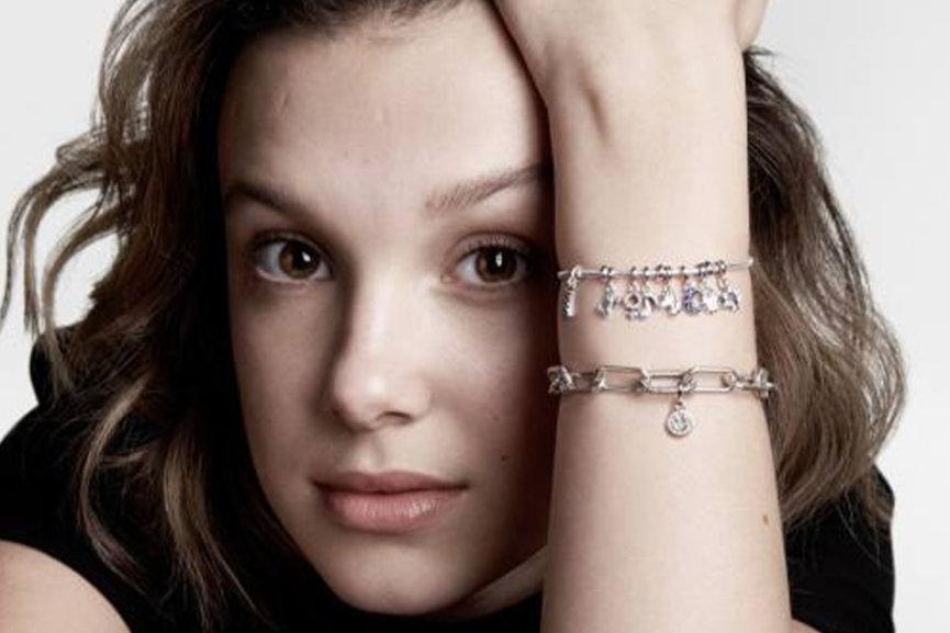 A close up of a girls face, her arm is visible with two bracelets on it.