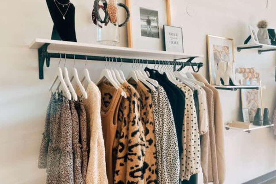 A rack of designer clothing hanging off of a wall