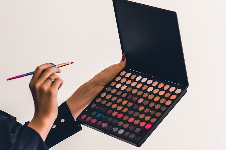 A woman holding a makeup pallete and a make up brush