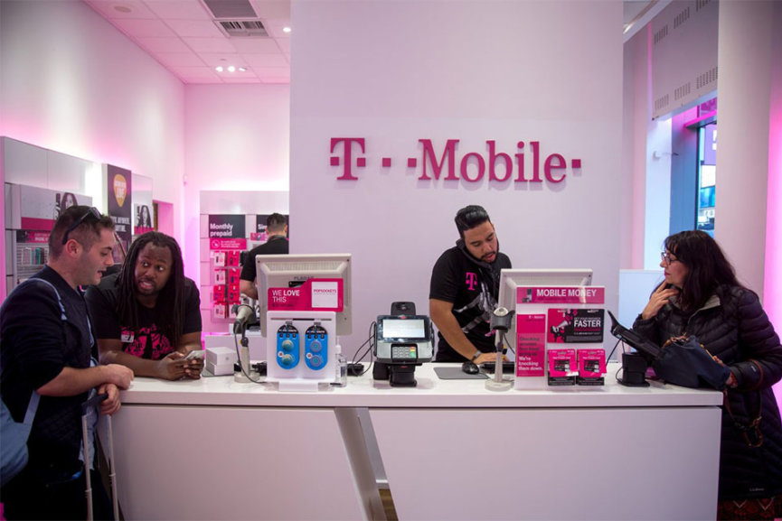 Several people trying phones in the T Mobile showroom