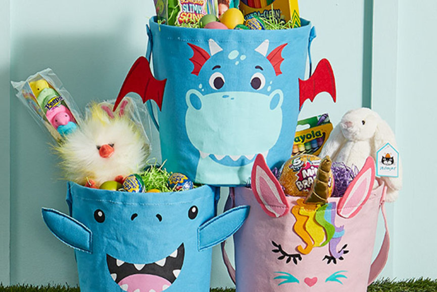Three baskets with cartoon characters on them. They are filled with candy, as well as arts and crafts supplies
