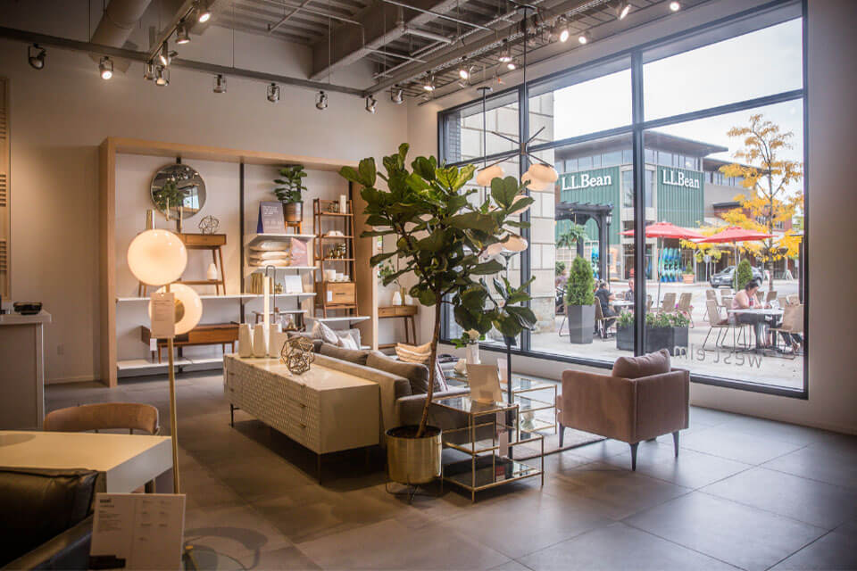 The West Elm showroom with arranged furniture and a large glass window at the back of the room