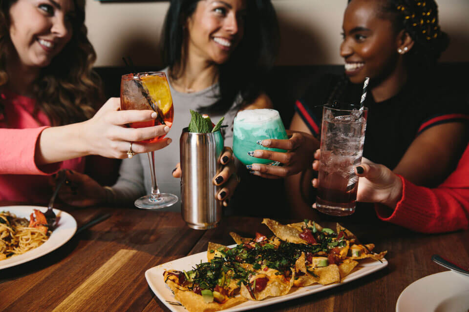 A group of woman toasting over a plate of appetizers