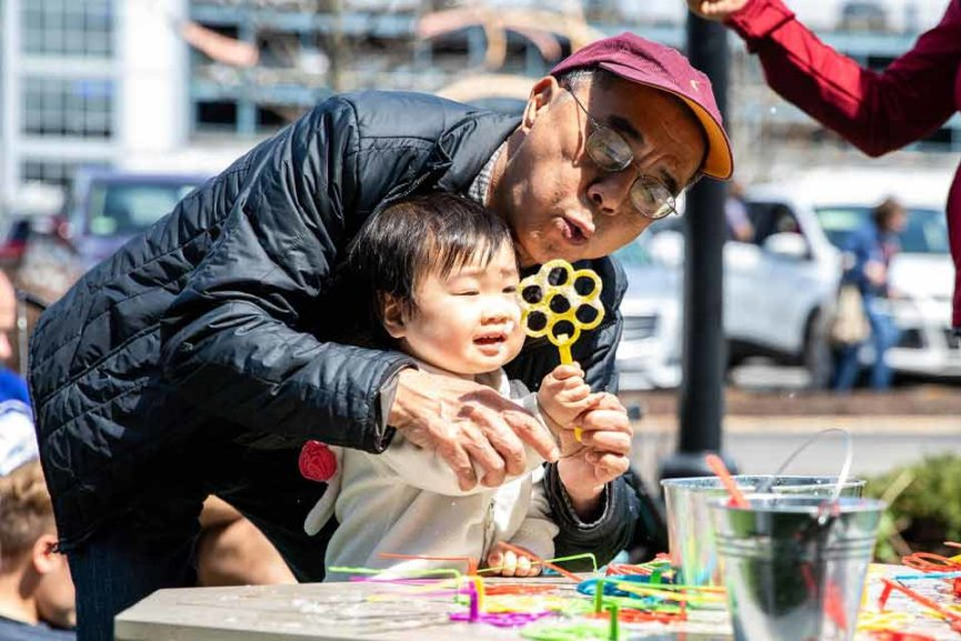 A grandfather blowing bubbles outside with his grand daughter