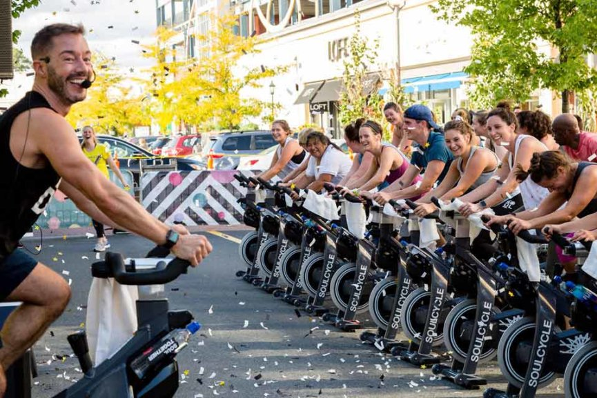A fitness instructor outside teaching a spin class with several students on spin bikes