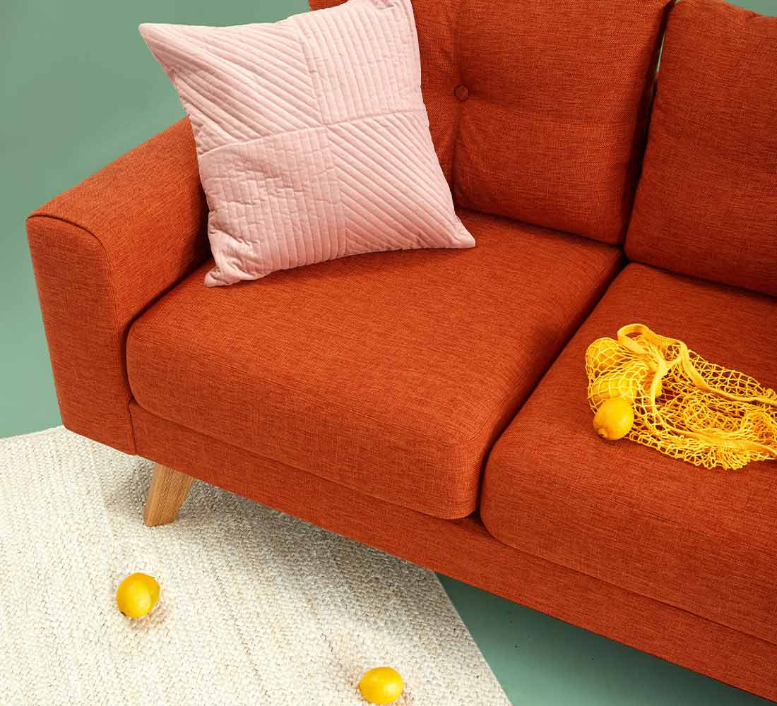 A red couch with a pink pillow on it