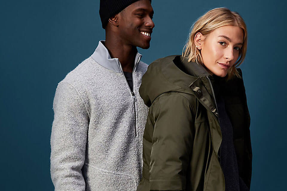 A man and woman standing close together wearing cold weather activewear